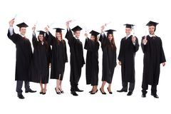 Gediplomeerde studenten die handen opheffen Stock Foto's