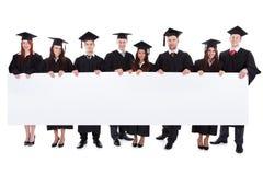 Gediplomeerde studenten die lege banner houden royalty-vrije stock fotografie