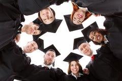 Gediplomeerde studenten die zich in cirkel bevinden die naar camera leunen stock afbeelding