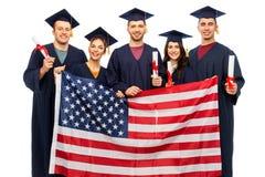 Gediplomeerde studenten met diploma's en Amerikaanse vlag royalty-vrije stock foto