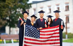 Gediplomeerde studenten met diploma's en Amerikaanse vlag royalty-vrije stock afbeeldingen