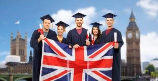 Gediplomeerde studenten met diploma's en Britse vlag royalty-vrije stock foto's