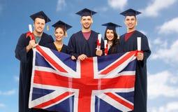 Gediplomeerde studenten met diploma's en Britse vlag stock foto's