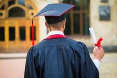 Gediplomeerde studentenhanden die diploma van de rug houden royalty-vrije stock afbeelding