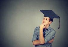 Gediplomeerde studentenmens die in GLB-toga omhoog denkend kijken stock afbeeldingen