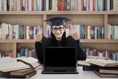 Gediplomeerde vrouw die duimen in bibliotheek opgeven Royalty-vrije Stock Afbeeldingen