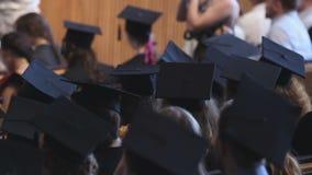 Gediplomeerden die aan de toespraak van de universitaire rector bij ceremonie, gelukkige toekomst luisteren stock video
