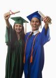 Gediplomeerden in GLB en toga met diploma royalty-vrije stock foto's