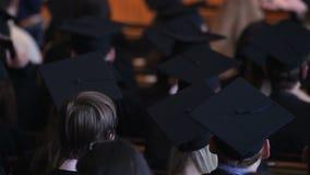 Gediplomeerden van officiële ceremonie worden vermoeid die waaien met academische kappen die stock footage