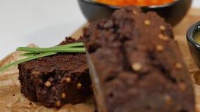 Gedobbelde boter, kaviaar, zwart brood De kom van rode kaviaar met lepel diende met gesneden brood, boter en kruiden op wit stock video