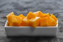 Gedobbelde die mangokubussen op een witte schotelclose-up worden geplaatst en worden gediend Royalty-vrije Stock Afbeelding