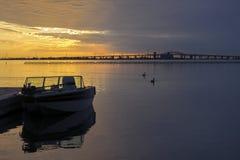 Gedokt die motorboot tegen een briljante zonsopganghemel wordt gesilhouetteerd, B royalty-vrije stock afbeelding