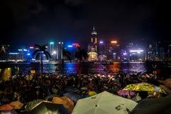 Gedrängtes Leute Wartenationaltag-Feuerwerk im Regen in Ufergegend von Victoria Harbour von Hong Kong Stockbilder