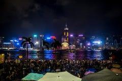 Gedrängtes Leute Wartenationaltag-Feuerwerk im Regen in Ufergegend von Victoria Harbour von Hong Kong Stockfoto