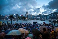 Gedrängtes Leute Wartenationaltag-Feuerwerk im Regen in Ufergegend von Victoria Harbour von Hong Kong Stockfotos