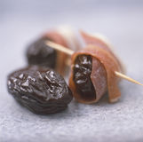 Gedroogde pruimen die in ruwe ham worden gerold Stock Foto