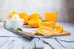 Gedrukt jus d'orange en verse sinaasappelenvruchten op wit houten t stock foto