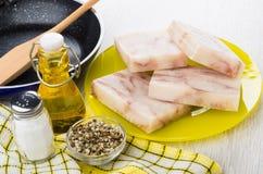 Gedrukt ruw pollock, plantaardige olie, zout, specerij, pan stock afbeeldingen