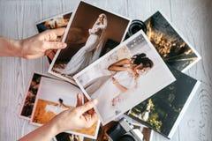 Gedrukte huwelijksfoto's met de bruid en de bruidegom, een uitstekende zwarte camera en vrouwenhanden met twee foto's stock afbeeldingen