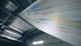 Gedrukte krant die op een rollende transportband, drukkantoorbenodigdheden gaan stock videobeelden