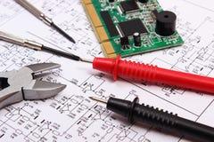 Gedrukte kringsraad, precisiehulpmiddelen en kabel van multimeter op diagram van elektronika Stock Afbeelding