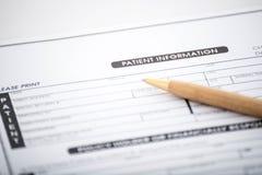Geduldige Informationsform und -stift auf Schreibtisch, medizinischer Fragebogen Lizenzfreies Stockfoto
