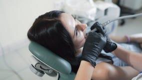 Geduldige Lügen im zahnmedizinischen Stuhl während der zahnmedizinischen Behandlung mit moderner Ausrüstung, Zeitlupe stock footage