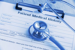 Geduldige medische geschiedenis op een klembord met stethoscoop en een blauwe ballpoint Stock Afbeeldingen