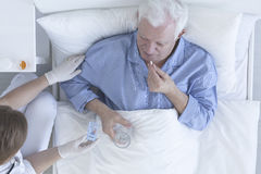 Geduldige nehmende Pille mit Glas Wasser Lizenzfreie Stockbilder