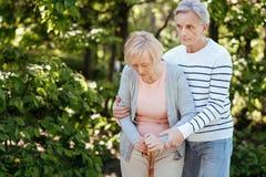 Geduldiger Mann im Ruhestand, der draußen ältere Frau stützt Stockfotos