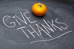 Geef dankherinnering op bord met pompoen en pompoenen stock foto