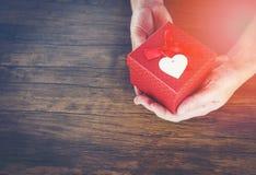 Geef de Liefdemens die kleine rode huidige doos in handen met Hart houden voor de dag die van liefdevalentijnskaarten een giftdoo royalty-vrije stock afbeelding