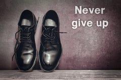 Geef nooit op bruine raad en het werkschoenen op houten vloer op stock foto's