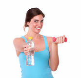 Geeignete anhebende Gewichte der jungen Frau und Wasserflasche Stockfotografie