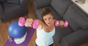 Geeignete anhebende Gewichte der jungen Frau zu Hause Stockbild
