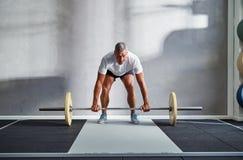 Geeignete anhebende Gewichte des älteren Mannes allein in einer Turnhalle stockfotografie