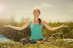 Geeignete blonde junge Frau der Schönheit, die auf der Natur mit Augen meditiert Stockfoto