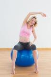 Geeignete blonde schwangere Frau, die auf Übungsball sitzt Stockfoto