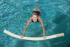 Geeignete blonde Schwimmen mit Schaumrolle Lizenzfreie Stockbilder