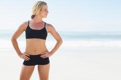 Geeignete blonde Stellung auf dem Strand Stockfotografie
