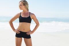 Geeignete blonde Stellung auf dem Strand Stockfotos