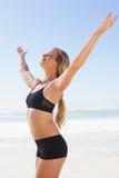 Geeignete blonde Stellung auf dem Strand mit den Armen ausgestreckt Stockbilder