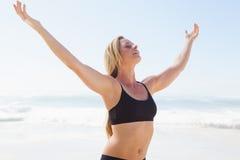 Geeignete blonde Stellung auf dem Strand mit den Armen ausgestreckt Lizenzfreies Stockbild