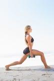 Geeignete Blondine, die belastete Laufleinen auf dem Strand tut Stockbilder