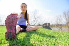Geeignete Eignungsfrau, die draußen Übungen ausdehnt Stockfoto