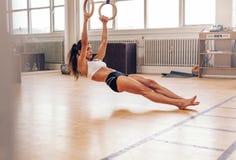 Geeignete Frau der Junge, die auf gymnastischen Ringen hochzieht Stockfotografie