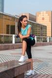 Geeignete Frau der Junge, die eine Pause nachdem dem Trainieren oder dem Laufen macht Eignungsmädchen, das draußen auf Stadtstraß stockfotos