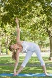 Geeignete Frau der Junge, die ihren Körper mit Yogahaltung ausdehnt Stockbilder