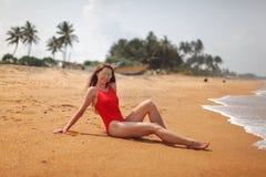 Geeignete Frau der Junge im roten Badeanzug, der auf den nassen Sandstrand wi sitzt stockfotos