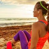 Geeignete Frau der nachdenklichen Junge auf der Küste, die nach Training sich entspannt lizenzfreies stockbild